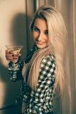 性感的白肤金发的妇女垂直的画象有杯的马蒂尼鸡尾酒在 图库摄影