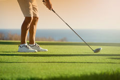 Ο παίκτης γκολφ πρόκειται να τοποθετήσει στο σημείο αφετηρίας μακριά στο ηλιοβασίλεμα Στοκ Φωτογραφία