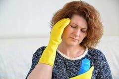 有头疼的妇女在清洗房子以后 库存图片