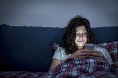使用智能手机的微笑的女孩在床 免版税库存照片