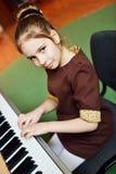 女孩一点钢琴使用 免版税库存图片