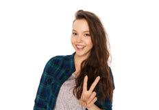 显示和平标志的愉快的微笑的十几岁的女孩 免版税图库摄影