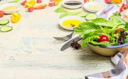 与年轻莴苣叶子和各种各样的穿戴的成份的健康蔬菜沙拉盘在轻的木背景 图库摄影