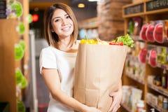 有一个购物袋的逗人喜爱的妇女在商店 免版税库存图片