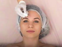 审查一个年轻女性客户的面孔美容师在温泉沙龙 美容师去除患者的面罩 免版税库存图片