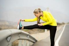 炫耀舒展腿肌肉的妇女在柏油路的连续锻炼以后有干燥沙漠风景的在坚硬健身训练上 免版税库存图片