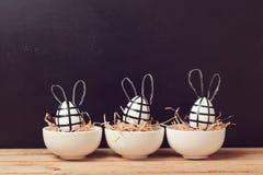 与兔宝宝耳朵的现代复活节彩蛋装饰在黑板 创造性的复活节背景 库存图片