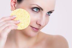 美丽的妇女去除面孔的构成海绵 免版税库存照片