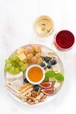 乳酪、果子、酒和快餐在板材,垂直的顶视图 库存图片