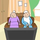 观看电视老人和妇女的老夫妇坐沙发家 库存照片