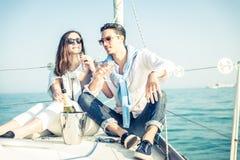 夫妇在小船的饮料香槟 免版税库存图片