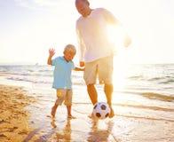 Сын отца играя концепцию лета пляжа футбола Стоковая Фотография RF