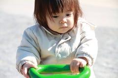 跷跷板的日本女婴 免版税库存照片