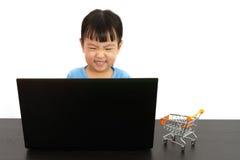 使用膝上型计算机的中国小女孩 免版税库存照片