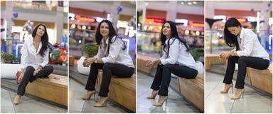 有男性白色摆在购物中心的衬衣和长裤的可爱的妇女 美丽的时兴的女孩坐长凳 库存照片