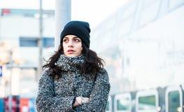 Красивая девушка стоя около железнодорожного вокзала пробуя держать назад ее разрывы - близкое поднимающее вверх - вид спереди Стоковое фото RF