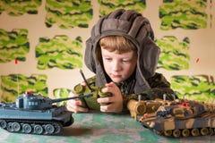 演奏玩具军事坦克的男孩 免版税库存图片