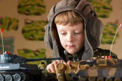演奏玩具军事坦克的男孩 库存图片
