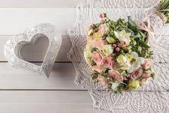 玫瑰和小苍兰美丽的婚礼花束与心脏在白色木背景、背景华伦泰的或婚礼之日 免版税库存照片