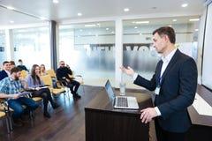 站立在论坛和演讲为学生的确信的英俊的老师 免版税库存照片