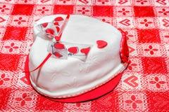 与红色心脏丝带的白色心脏形状蛋糕 免版税库存照片
