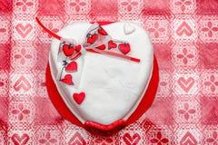与红色心脏丝带的白色心脏形状蛋糕 库存图片