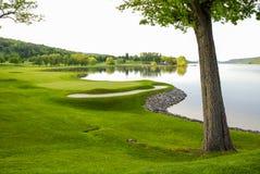 Зеленый цвет поля для гольфа спокойным озером Стоковые Фотографии RF