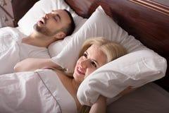 有打鼾在睡眠的丈夫的妻子 免版税库存照片