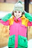 相当正面女孩在户外明亮的五颜六色的滑雪服冬天,在降雪期间的外部 免版税库存照片