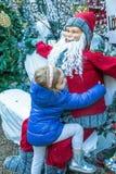 有桃红色箍的逗人喜爱的白肤金发的女孩在她的头发和蓝色外套在圣诞老人附近 免版税库存照片
