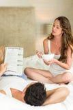年轻夫妇读书报纸和有早餐在床上 库存照片