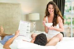 年轻夫妇读书报纸和有早餐在床上 免版税库存照片