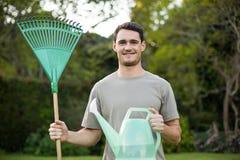 站立与一把从事园艺的犁耙和喷壶的年轻人画象 免版税图库摄影