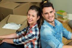 紧接坐在他们的新房里的年轻夫妇 免版税库存照片