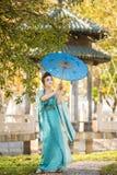 有一把蓝色伞的美丽的艺妓在绿色苹果树附近 库存照片