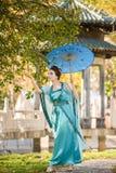 有一把蓝色伞的美丽的艺妓在绿色苹果树附近 图库摄影