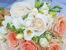 在桃红色和白玫瑰花束的两个婚戒 免版税库存图片