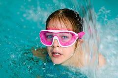 桃红色风镜面具的逗人喜爱的愉快的女孩在游泳池 免版税图库摄影