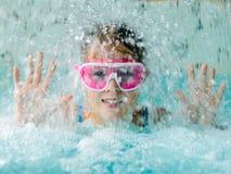 桃红色风镜面具的逗人喜爱的愉快的女孩在游泳池 免版税库存图片