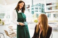 供食咖啡的微笑的女服务员 免版税库存图片