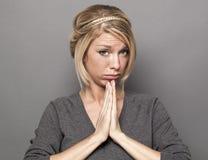 哀伤的年轻白肤金发的妇女的祈祷的概念 库存照片