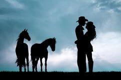Ζεύγος και άλογα στο ηλιοβασίλεμα Στοκ εικόνα με δικαίωμα ελεύθερης χρήσης