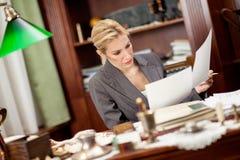 坐在办公室和工作的一张桌上的女实业家 库存图片