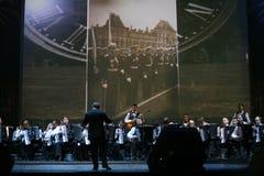 在阶段、乐队的音乐家和独奏者手风琴师(泛音乐队)在指挥下警棒  免版税库存照片