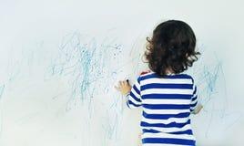 与蜡笔颜色的卷曲逗人喜爱的小的女婴图画在墙壁上 孩子工作  图库摄影