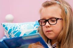 戴眼镜的女孩读在床上的 免版税图库摄影