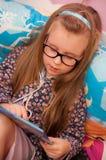 戴眼镜的女孩读在床上的 免版税库存照片
