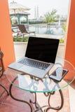 便携式计算机、电话、书和植物在桌上在游泳 库存照片