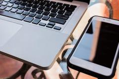 便携式计算机、电话、书和植物在桌上在游泳 免版税库存图片