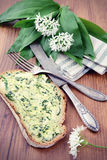 在桌上的野生蒜与银器和切片面包用黄油 免版税库存图片